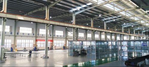 婺江装饰集团目前已经具备年产20万平方米的玻璃幕墙、金属门窗生产能力。图中远处的工人在进行门窗加工作业,近处为玻璃幕墙打胶房。