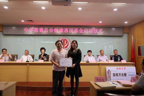图为中华慈善总会秘书长边志伟向魏东总裁颁发捐赠荣誉牌