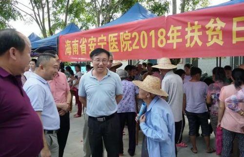 图为海南省卫生健康委员会副主任王锋(中)与村民交流。