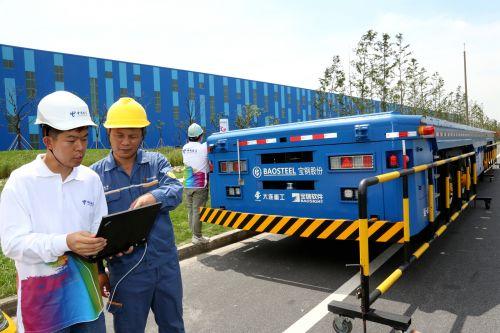 中国电信上海公司移动互联网部的技术人员与宝钢股份宝山基地运输部的管理人员一起查看无人重载框架车的5G信号接收情况。王万隆摄影