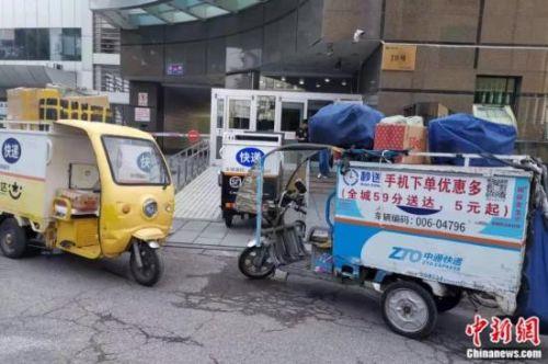 北京东城区,多家公司快递车在进行投递。张旭 摄