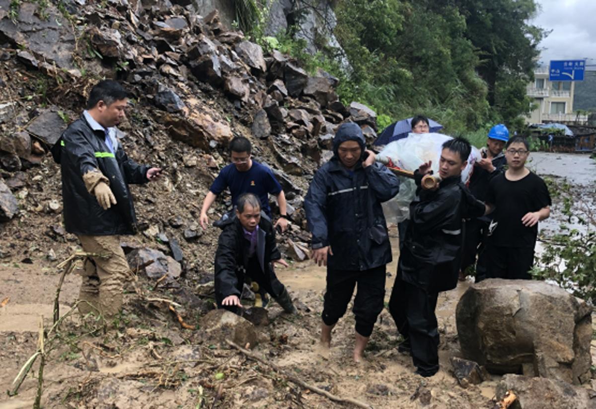 树木拦腰折断,道路塌方,救援人员踩着淤泥冒雨扛着担架轮流接力。