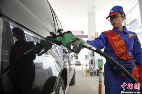 山西太原一加油站,工作人员为车主加油。中新社发 韦亮 摄