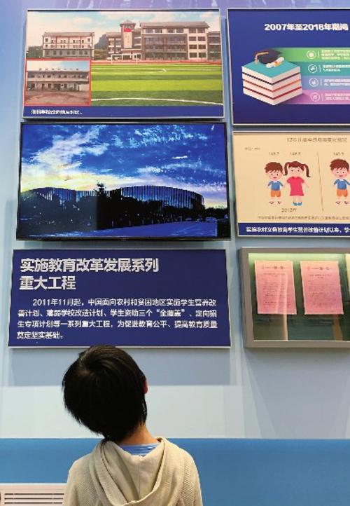 70周年成就展上,小观众正仔细观看教育改革发展相关图示。中国经济导报记者蔡若愚/摄
