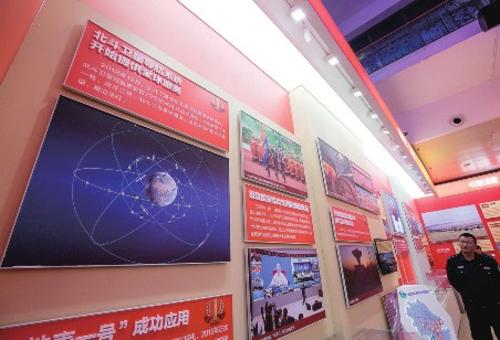 """在""""伟大历程辉煌成就——庆祝中华人民共和国成立70周年大型成就展""""上,一幅介绍北斗系统的展板吸引了不少参观者的目光。中国经济导报记者苗露/摄"""