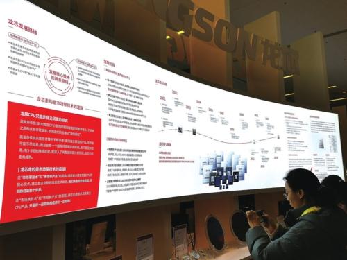 """图为在""""2019龙芯产品发布暨用户大会""""展览区,观众正在观看展板,了解龙芯中科的发展历程。王晓涛/摄"""