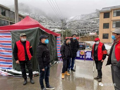 志愿者在石璜镇西白山村卡点雪中坚守