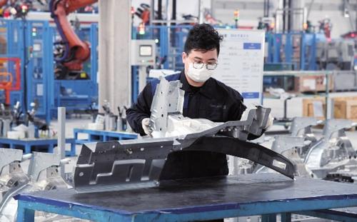 战疫情 稳增长    2月10日是春节后复工第一天,工作人员在北京一家汽车零部件生产企业对产品进行检验。新华社
