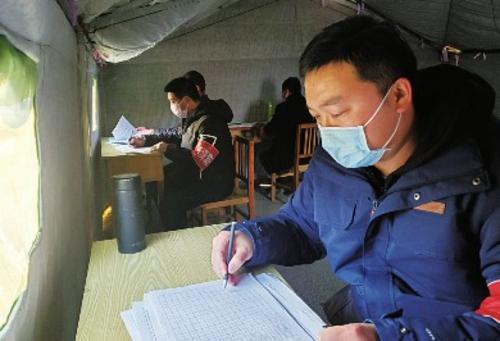 驻村第一书记郑慧涛(右一)在疫情防控检查点整理人员车辆进出记录。赵二军/供图