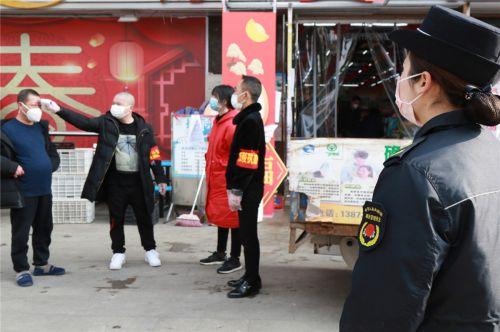 2020年2月13日,湖北恩施,城区一家超市的防疫工作人员在给前来购物的市民测量体温。谭华 摄