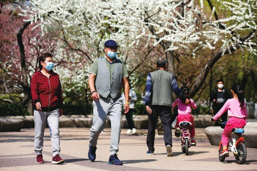 走到户外享受春天    3月23日,北京风和日丽,戴着防护口罩的人们走到户外,乐享春和景明。齐赢会经济导报记者  苗 露/摄