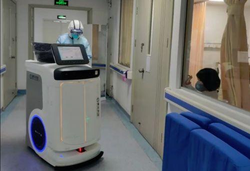 图为在医院的隔离病房,一个小女孩趴在窗边好奇地注视着走廊里的机器人。