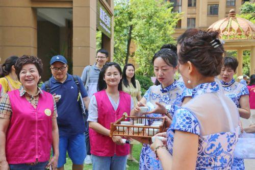 """和悦社区党委书记汪燕飞与正在进行茶艺表演的""""格姐""""。记者沈贞海 摄"""