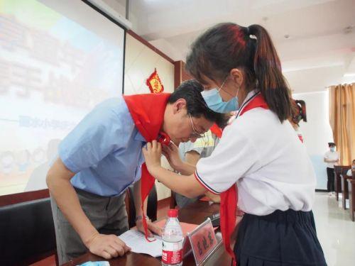在活动室,少先队员为吕伯伯等领导和老师敬献红领巾。