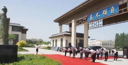 吕晓东在学校门口,和老师们一起参拜了孔子像。