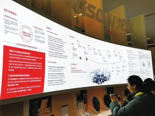 观众在龙芯产品发布暨用户大会展览区观看展板,了解龙芯中科的发展历程。中国经济导报记者王晓涛/摄