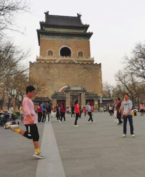 ⑩大年初十,位于北京中轴线的钟鼓楼文化广场上,一位健身高手把毽子踢向25度气温的空中。于进/摄
