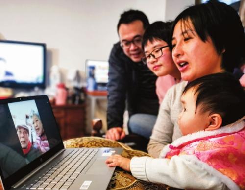 ①大年三十,留在北京过年的一家人通过视频给远在家乡的老人拜年。程晖/摄