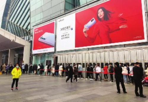⑥大年初二早晨,人们在北京西单大悦城门口排起长队,等待开门。钟铭/摄
