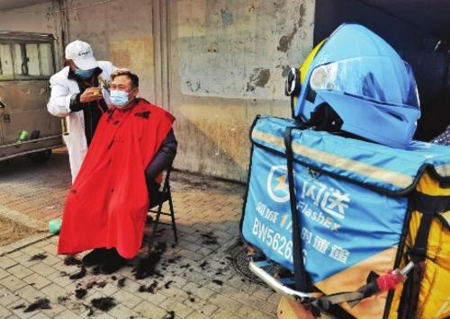 ③大年三十下午,一名快递小哥在北京六里桥立交桥下一处露天理发摊理发,准备干干净净迎新年。苗露/摄
