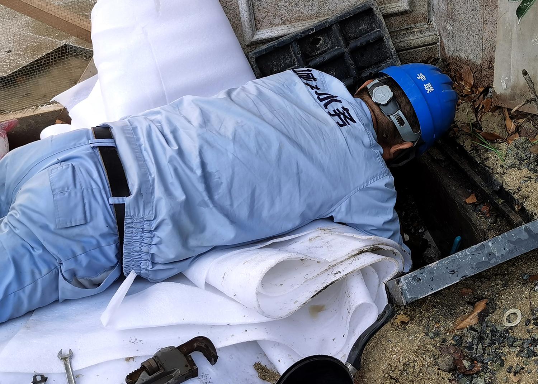 图为上海城投水务维修人员正趴在地上抢修供水管网。张先生供图
