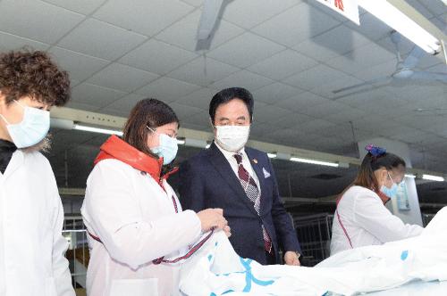 波司登集团董事局主席兼总裁高德康在防疫期间察看防护服生产。