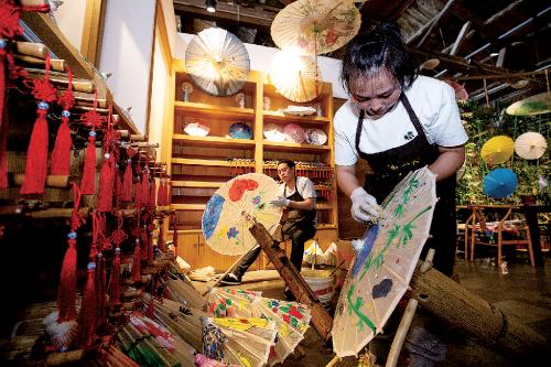 制伞匠人在杭州手工艺生态馆里给油伞涂刷桐油。中国经济导报记者苗露/摄