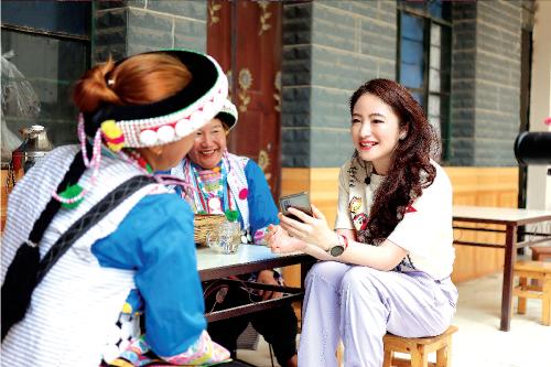 """科大讯飞高级副总裁杜兰博士和傈僳族老乡分享如何通过""""语言扶贫APP""""学普通话。"""